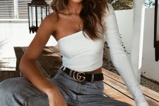 blue jeans, a statement belt, a white one sleeve top and white sneakers for a catchy look