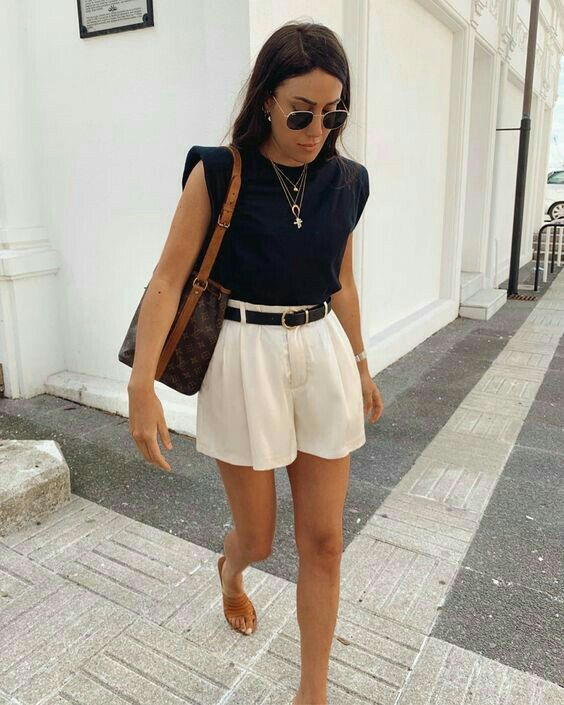 ivory pleated mini shorts, a top with accented shoulders, nude sandals and a dark bag plus layered necklaces