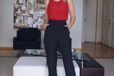 navy high waisted pants, a red sleeveless top, red ankle strap heels and red statement earrings