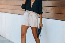 neutral paperbag waist shorts, a black shirt with a deep neckline, tan heels and a black clutch