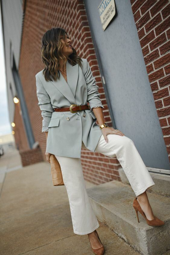 white flare jeans, a light green blazer as a top, a brown belt, brown shoes and a tan clutch