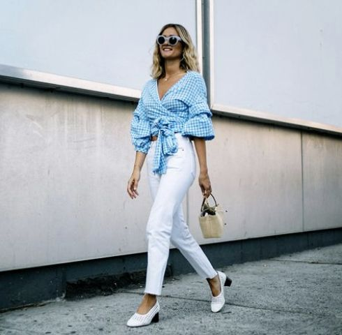 white jeans, a blue gingham wrap crop blouse with puff sleeves, white perforated shoes and a straw bag