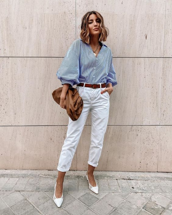white jeans, a blue shirt with puff sleeves, white shoes, a brown belt and a bag