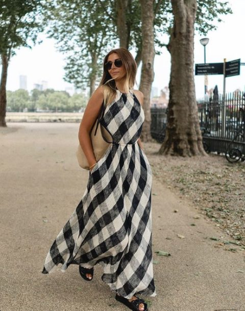 a black and white linen printed maxi dress with a halter neckline, black birkenstocks and a straw tote