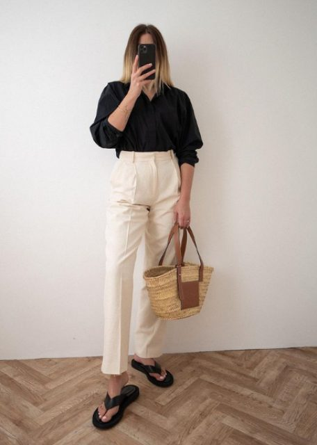 a black linen shirt, white high waisted trousers, black platform flipflops and a top handle straw bag
