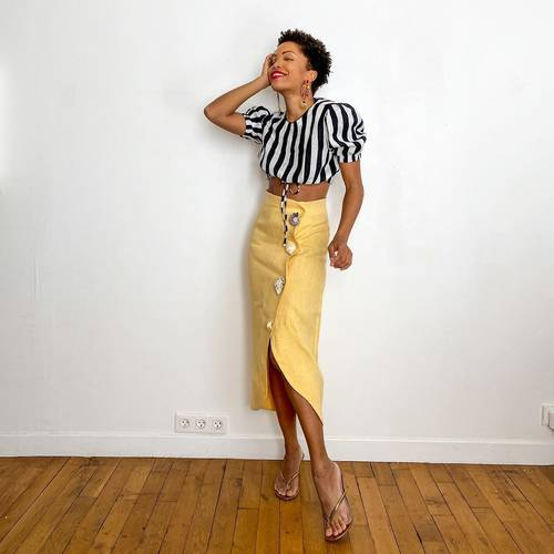 a black and white striped blouse with puff sleeves, a yellow high waisted midi skirt, nude heeled fliflops