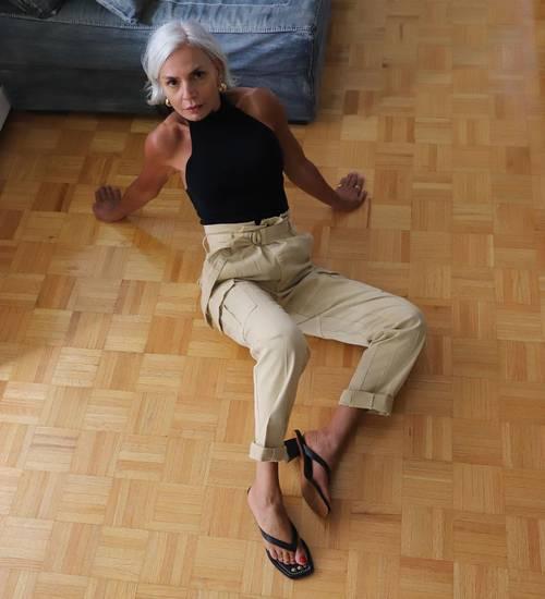 a black halter neckline top, tan paperbag waist trousers and black heeled flipflops
