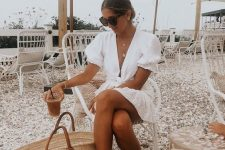 04 a white mini dress with puff sleeves, brown slippers, a large straw tote are ideal for a vacation