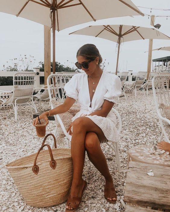 a white mini dress with puff sleeves, brown slippers, a large straw tote are ideal for a vacation