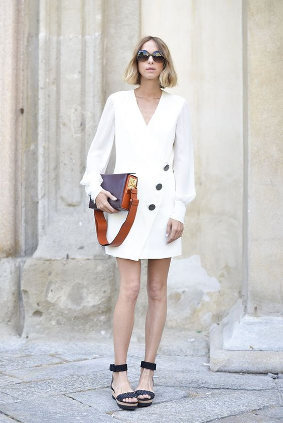 a stylish summer work look with a white blazer dress with long sleeves, black platform shoes and a two tone bag