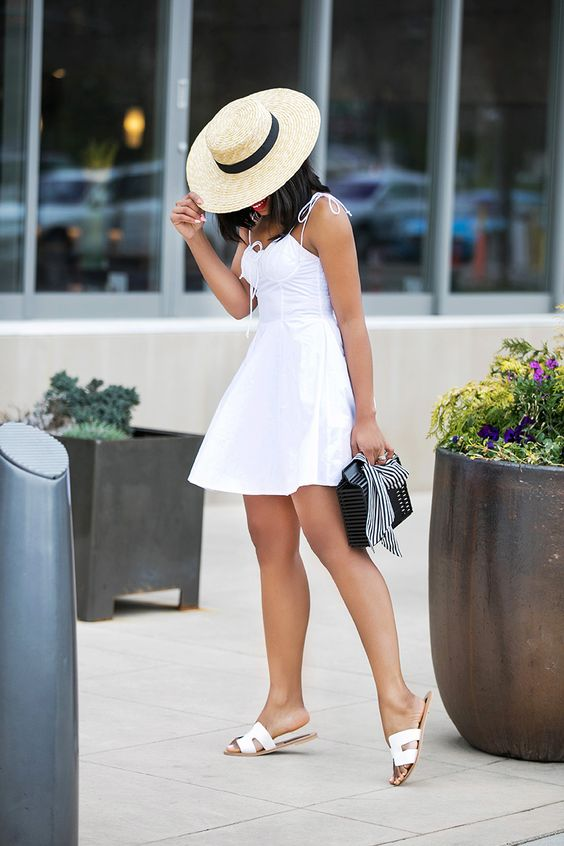 a white A-line mini dress with bows on the shoulders, white slippers, a black bag with striped ribbons, a hat