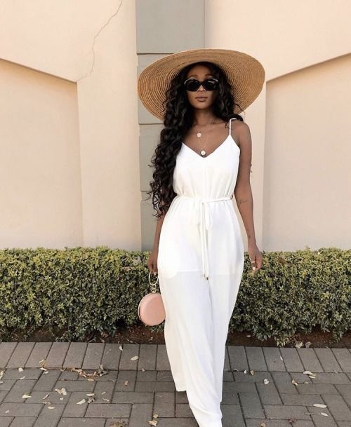 a white linen maxi dress with a sash, layered necklaces, a wide brim hat and a tiny pink round bag