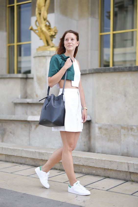 an asymmetrical green and white crop top, a white denim mini, white sneakers and a black bag