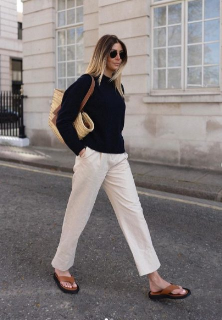 white pants, a black long sleeve tee, brown platform flipflops and a straw bag for a cooler summer day