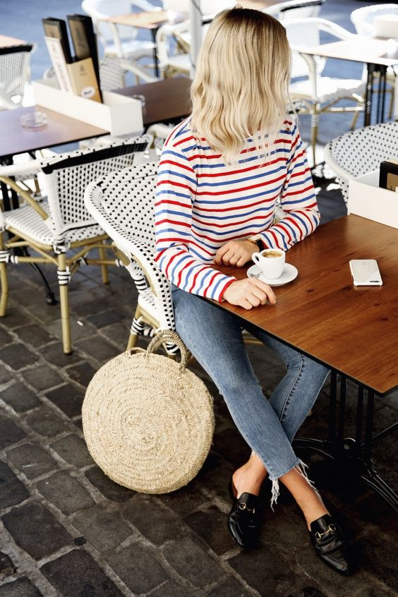 a bright striped long sleeve top, skinny jeans, black mules and a round straw bag for a cold summer day