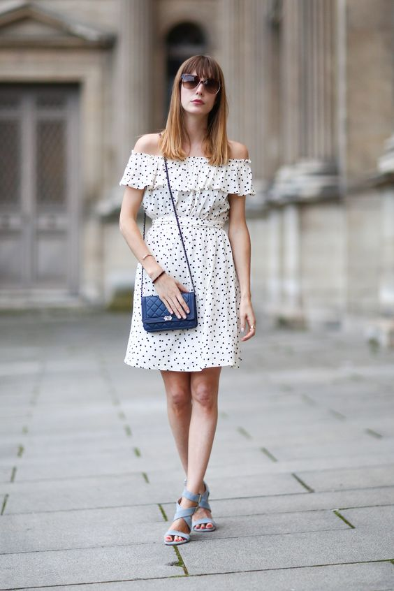 an off the shoulder polka dot over the knee dress, blue lace up shoes, a navy bag for a romantic look