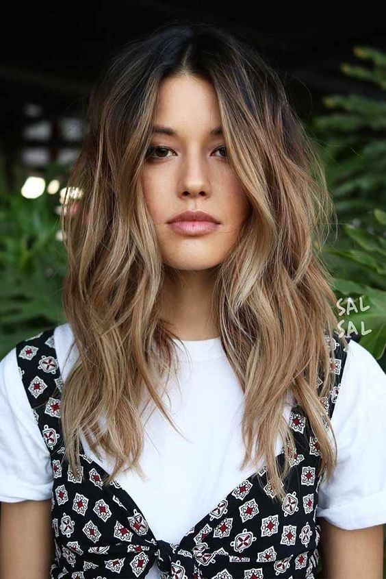 dark brunette hair with beautiful and messy waves and sunkissed balayage is a chic and pretty idea that looks rather natural