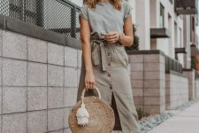 10 a grey t-shirt, an olive green button up paperbag waist skirt, pompom slippers and a round straw bag