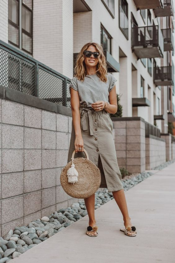 a grey t-shirt, an olive green button up paperbag waist skirt, pompom slippers and a round straw bag