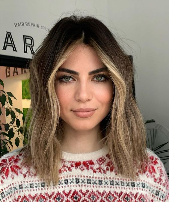 dark brunette hair with light sunkissed balayage and face framing higlights looks very chic and summer-inspired