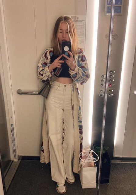a black crop top, white pants, white trainers, a colorful floral print kimono and a grey bag