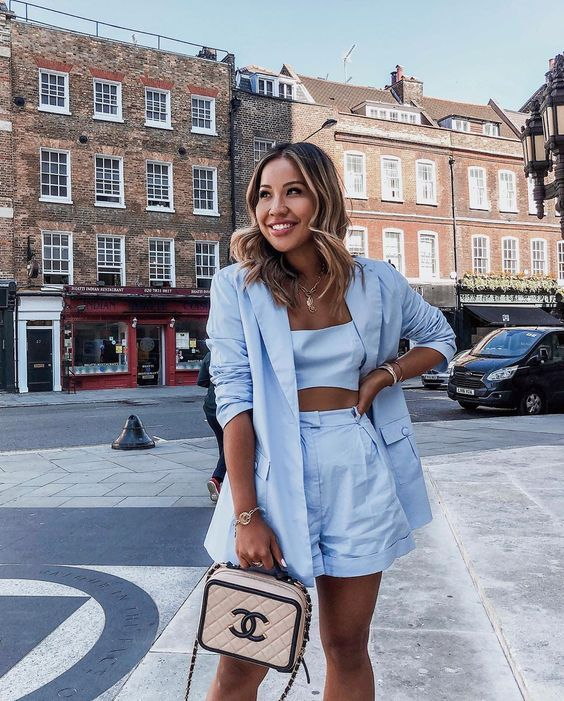 a blue linen three-piece suit with a crop top, wideleg shorts and a long blazer, a pink and black bag