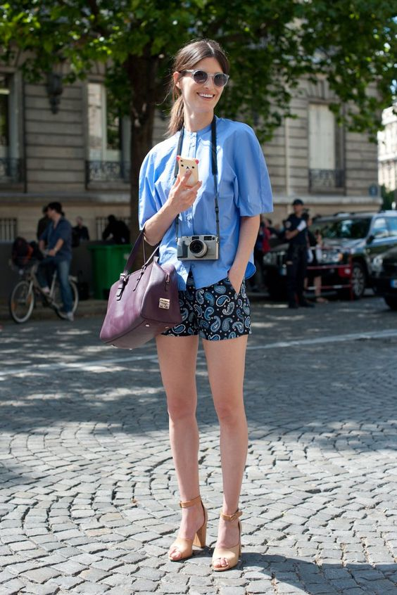 a bold blue shirt with short sleeves, printed mini shorts, a purple bag and ankle strap heels for summer