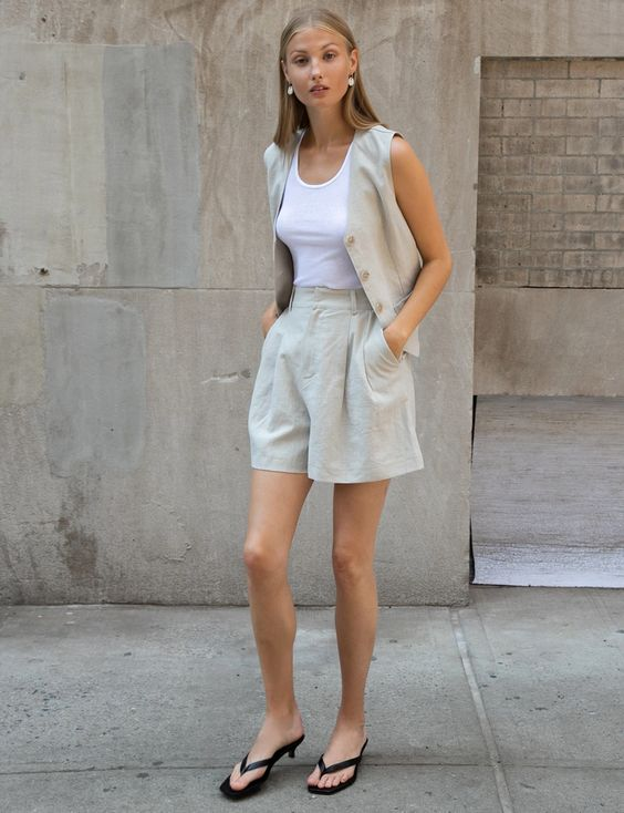 a summer work outfit with a grey linen suit with shorts and a waistcoat, a white top and black heeled flipflops