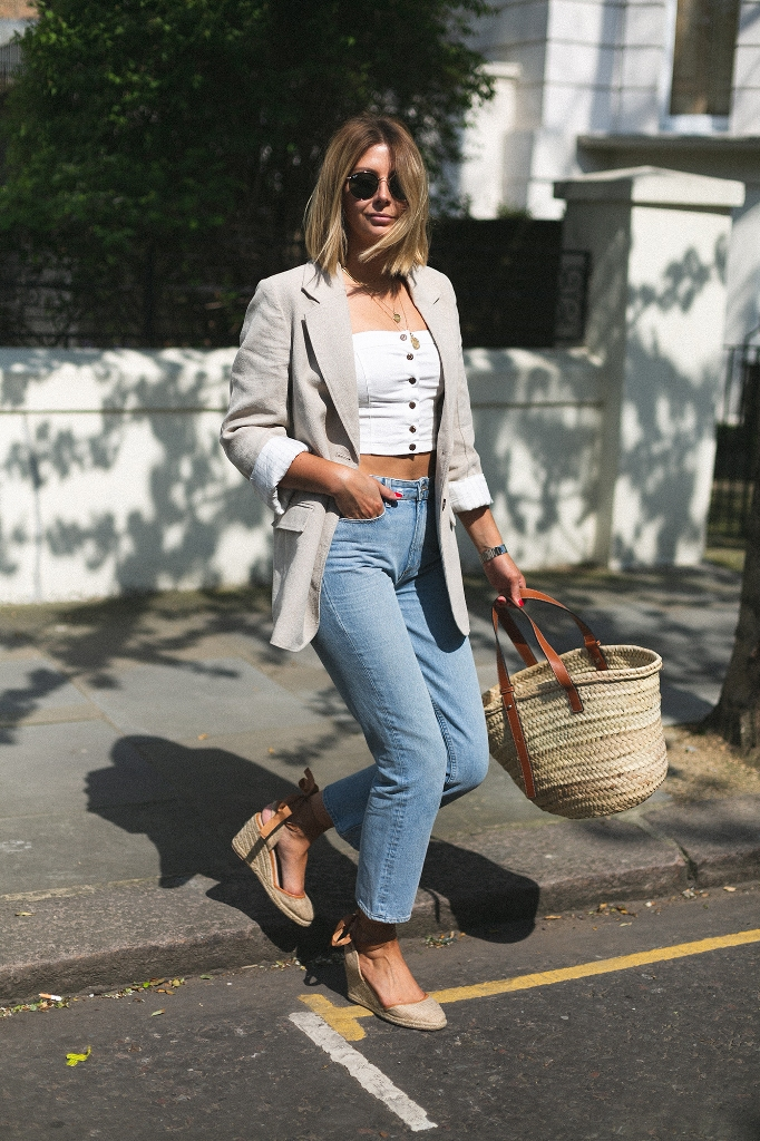 a white strapless crop top, blue jeans, espadrilles, a linen blazer and a straw tote for a chic summer look