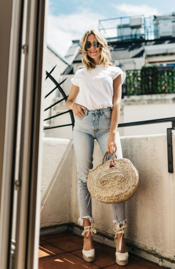 a white t-shirt, blue cropped jeans, espadrilles and a round straw bag for a casual and a bit girlish look