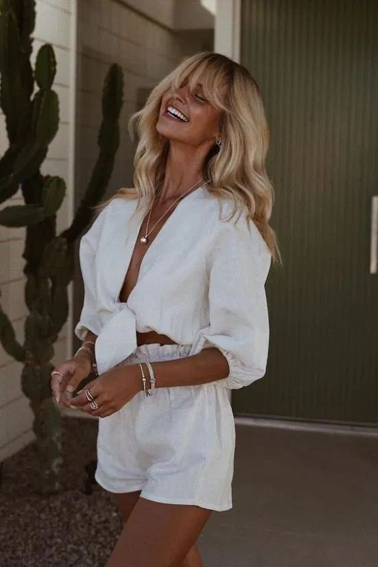 a cool summer vacation outfit with a white linen tied up blouse with puff sleeves and matching mini shorts plus a statement necklace