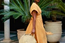 16 a yellow linen midi dress with short sleeves, a sash and faux fur slippers, a colorful headband and a round straw bag