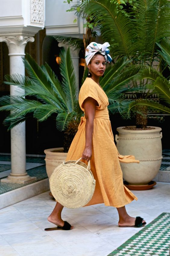 a yellow linen midi dress with short sleeves, a sash and faux fur slippers, a colorful headband and a round straw bag