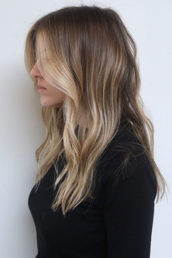 light brunette hair with sunkissed blonde higlights and with waves is a very actual and stylish idea
