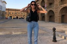 17 a black top and blue cropped jeans, black heeled flipflops and a small black bag
