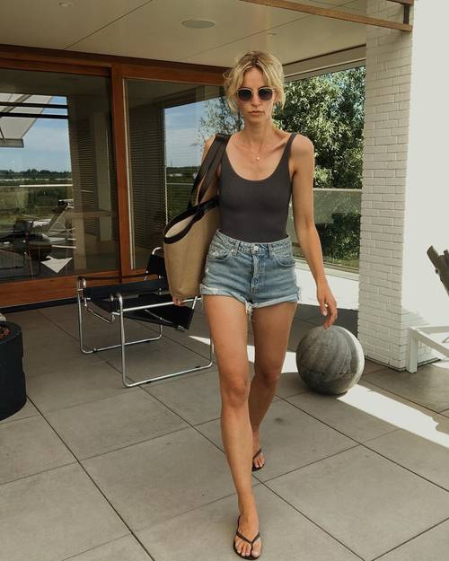 a black top, blue denim mini shorts, a large tote and black flipflops for an every day summer look