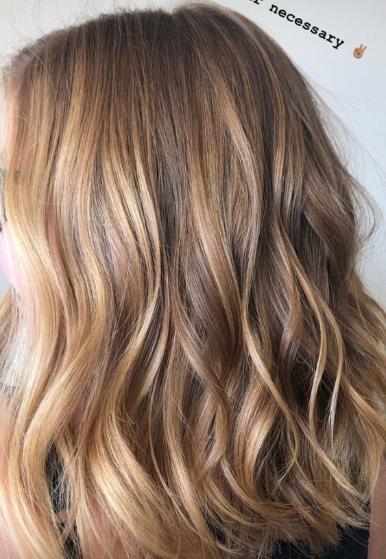 light brunette hair with blonde and sunkissed balayage and waves is a very cool beach-inspired option