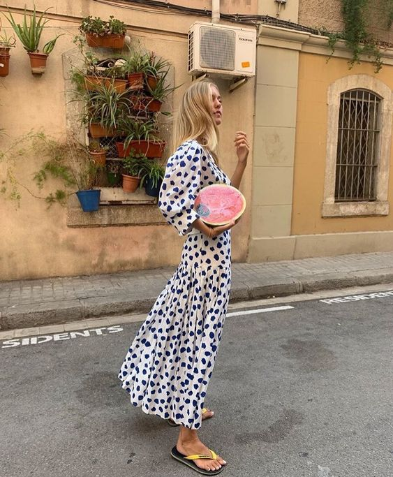 a midi white and navy dress with puff sleeves and yellow flipflops for a contrasting look