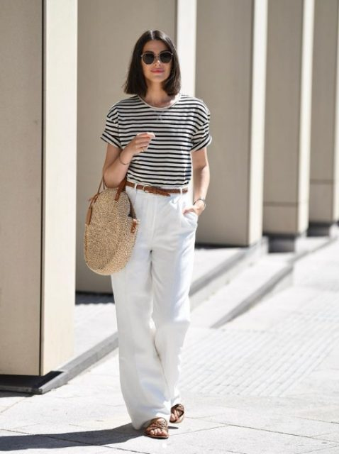 a striped t-shirt, white linen pants, brown slippers, a brown belt and a round woven bag