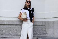 21 a minimalist summer outfit with a white t-shirt, a creamy maxi skirt with a slit, a creamy clutch and black flipflops