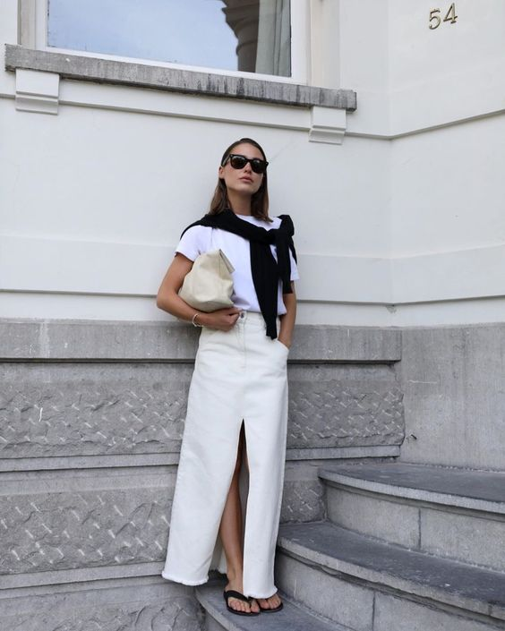 a minimalist summer outfit with a white t-shirt, a creamy maxi skirt with a slit, a creamy clutch and black flipflops