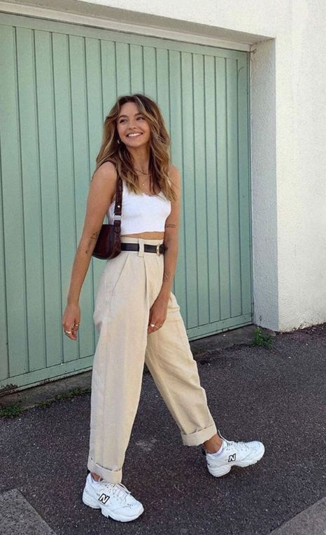 a white crop top, tan high waisted pants, black belts, white trainers, a brown baguette bag for summer