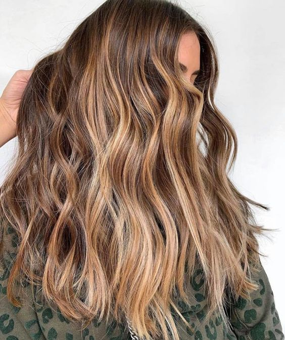 long wavy brunette hair with sunkissed balayage is a pretty idea for summer that doesn't require much maintenance