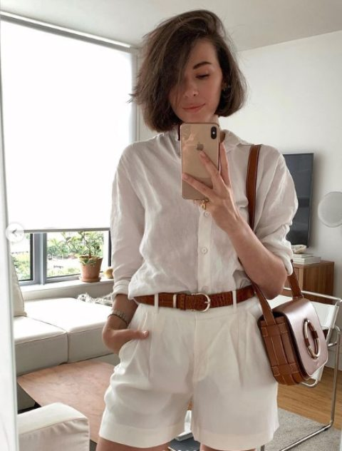 a white linen shirt, white linen shorts, a brown belt and a brown bag with a large ring on it