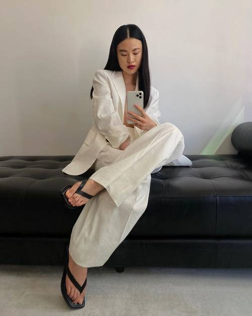 a white pantsuit with an oversized blazer, black flip flops are a stylish minimalist outfit to rock