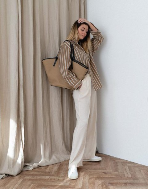 an oversized white and tan striped shirt, white linen pants, white sneakers and a neutral tote