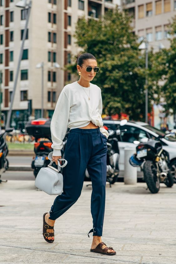 navy trousers, a white tied up long sleeve top, brown birkenstocks, a white bag for every day