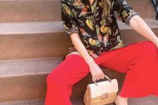 26 red trousers, a bold printed shirt, a straw and white color block bag and black flipflops