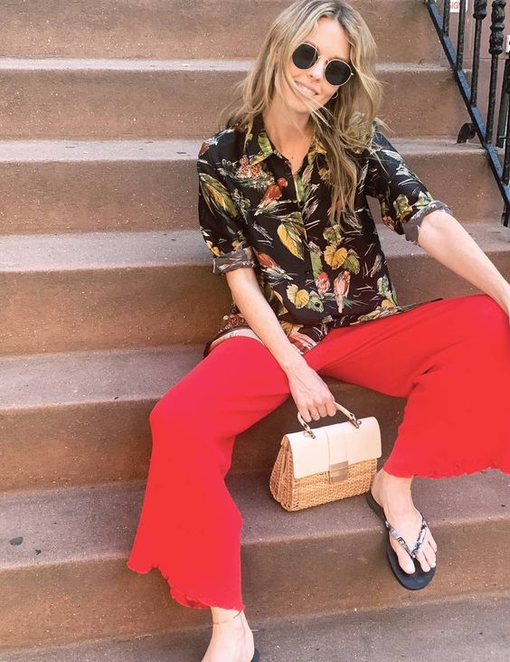 red trousers, a bold printed shirt, a straw and white color block bag and black flipflops
