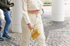 With beige belted trousers, snake printed heeled mules and yellow mini bag